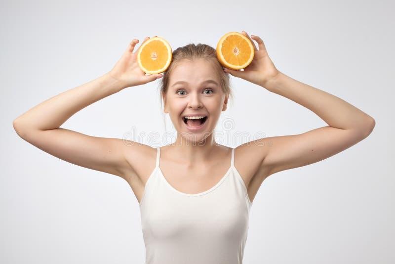 Schöne junge Blondine im weißen Hemd, das Stück von orange nahem ihr Hauptlächeln hält stockbilder