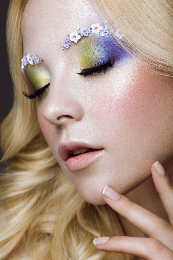 Schöne junge Blondine mit kreativer Make-upfarbe, -locken und -blumen auf Augenbrauen Schönes lächelndes Mädchen Art Makeup lizenzfreies stockfoto