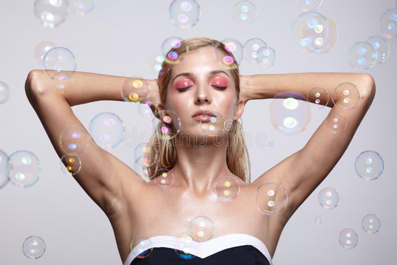 Schöne junge Blondine mit Seifenblasen auf grauem backgroun lizenzfreie stockbilder