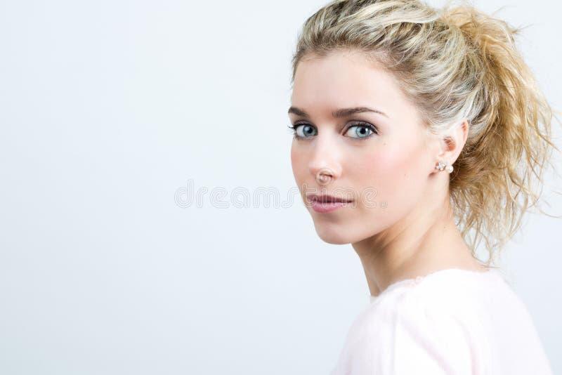 Schöne junge Blondine, welche die Kamera betrachten stockfotografie