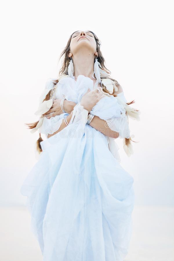 Schöne junge boho Frau im weißen Kleid und Federn, die an aufwerfen stockfoto