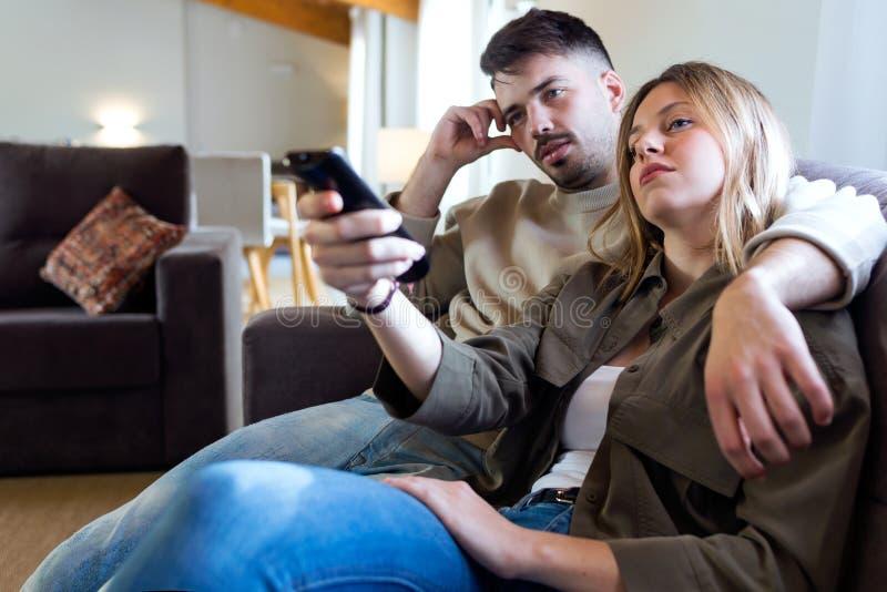 Schöne Junge bohrten die Paare, die zu Hause im Sofa fernsehen lizenzfreies stockfoto