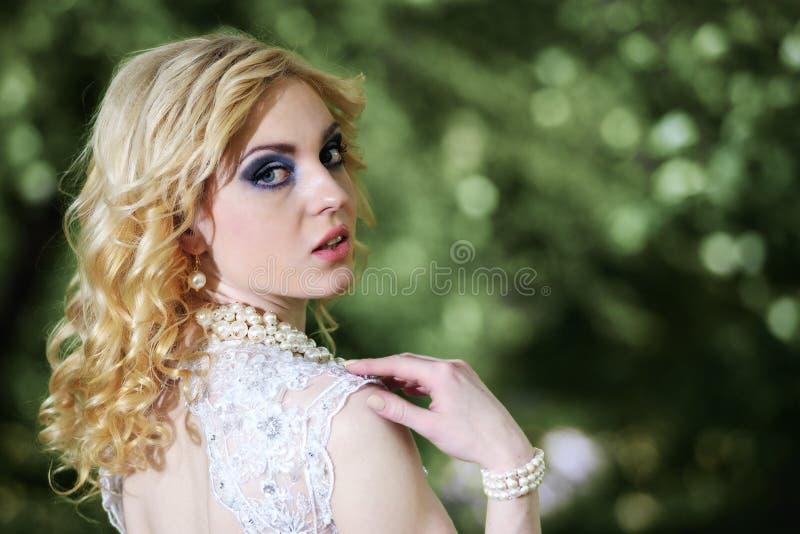 Schöne junge Braut des Porträts im weißen Kleid im Sommergrünpark stockfotos