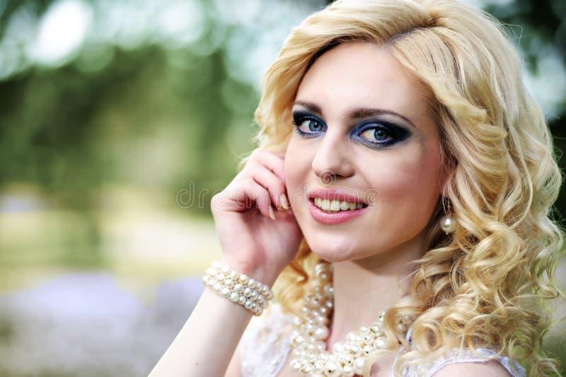 Schöne junge Braut des Porträts im weißen Kleid im Sommergrünpark stockbild