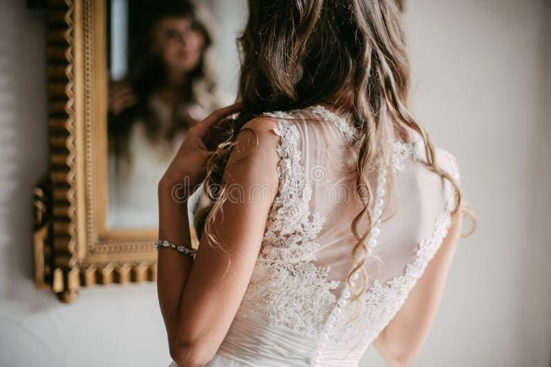 Schöne junge Braut, die im Spiegel schaut stockfoto