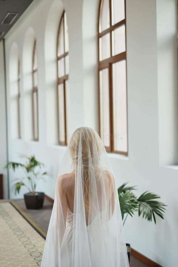 Schöne junge Braut in einem weißen Heiratskleid und -schleier, Stellung im Hotel und Warten auf den Bräutigam vor dem Heiratscere lizenzfreie stockfotografie