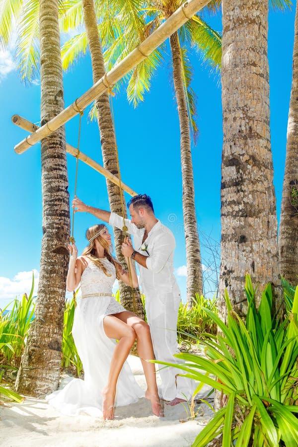 Schöne junge Braut in einem weißen Kleid und in einem Bräutigam unter einer Palme tr stockfotografie