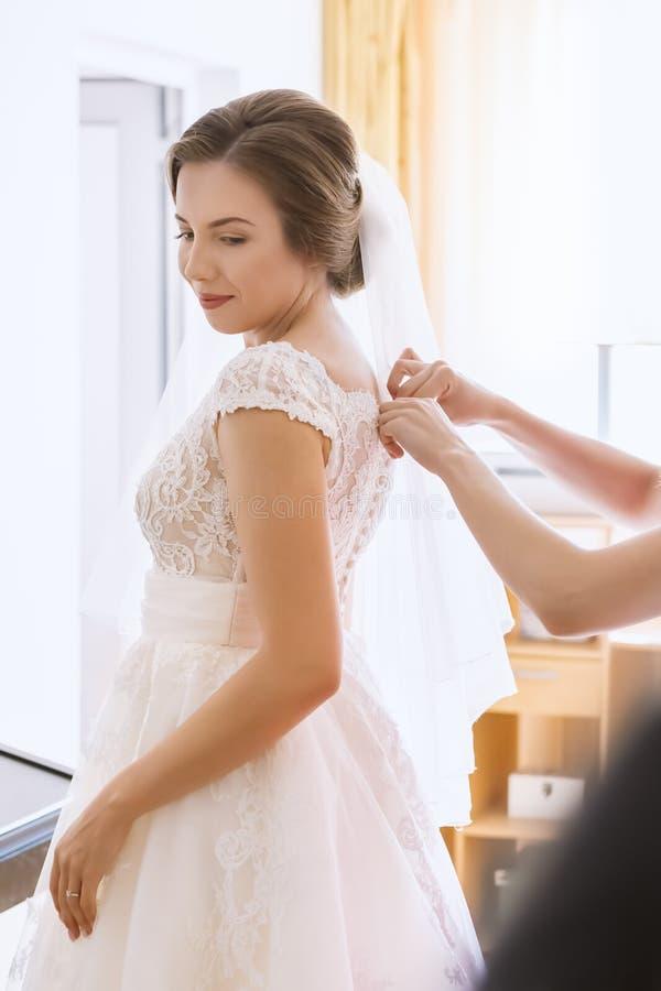 Schöne junge Braut im Hochzeitskleid im Wohnzimmer lizenzfreie stockfotografie