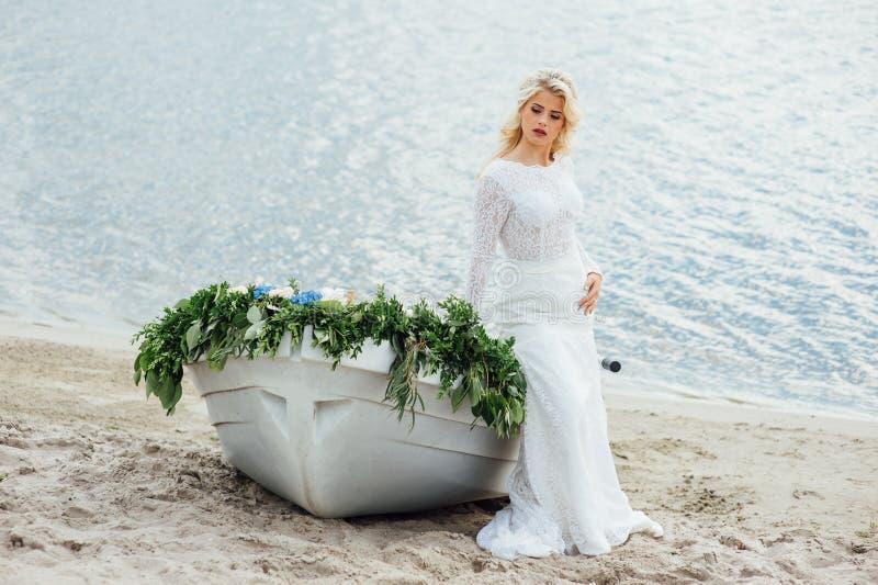 Schöne junge Braut im Luxushochzeitskleid lizenzfreie stockfotografie