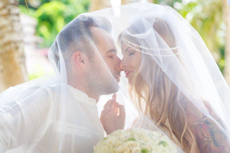 Schöne junge Braut im Schleier, mit Hochzeitsblumenstrauß von Weiß stockfotografie