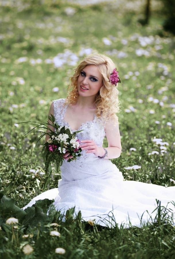 Schöne junge Braut im weißen Kleid sitzt Feld im Sommergrünpark lizenzfreies stockbild