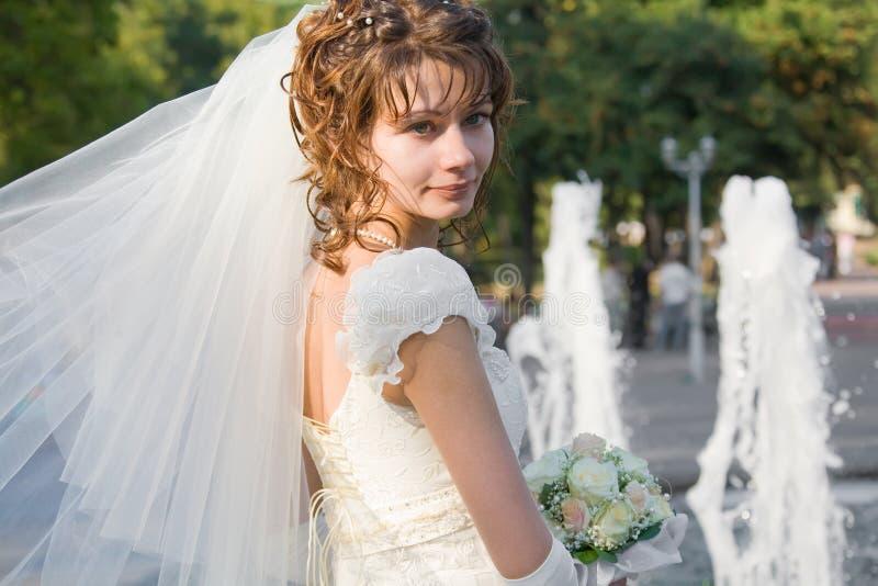 Schöne junge Braut mit Brunnen auf Hintergrund stockfoto