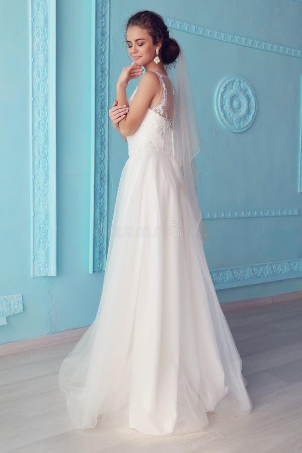 Schöne junge Braut mit dem dunklen gelockten Haar im luxuriösen Hochzeitskleid, das am Raum aufwirft stockfotos