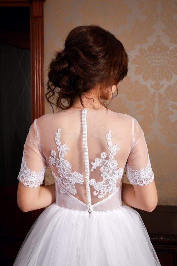 Schöne junge Braut mit den Brunettehaaren in einem Schlafzimmer Klassisches weißes Hochzeitskleid Nahaufnahmeporträt, Ansichtrück lizenzfreies stockbild