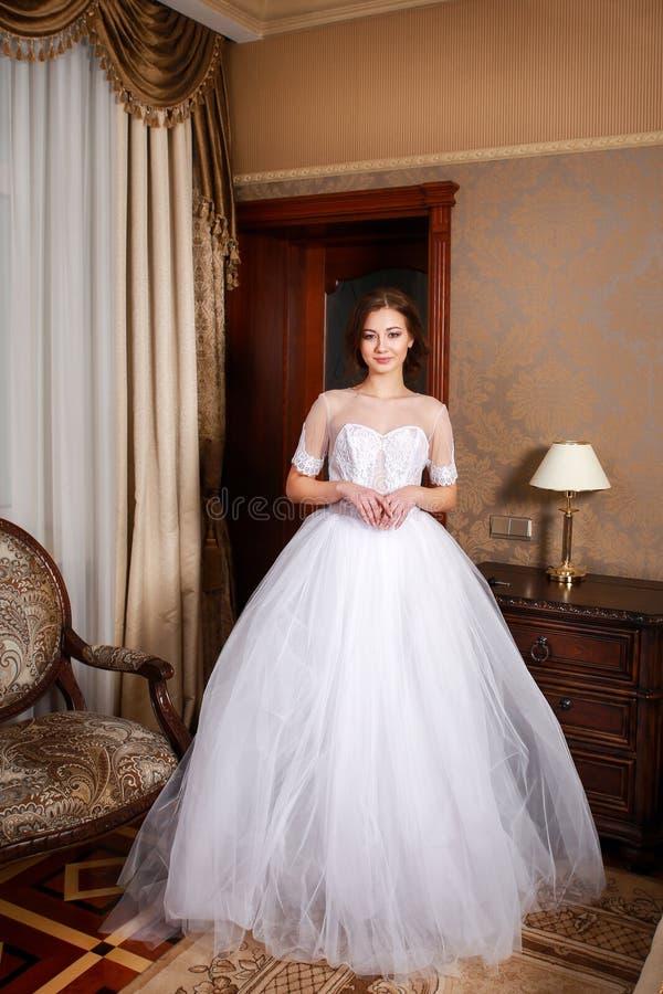 Schöne junge Braut mit den Brunettehaaren in einem Schlafzimmer Klassisches weißes Hochzeitskleid In voller Länge Portrait stockbild
