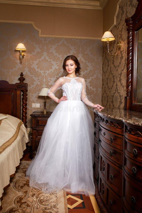 Schöne junge Braut mit den Brunettehaaren in einem Schlafzimmer Klassisches weißes Hochzeitskleid In voller Länge Portrait stockfotografie