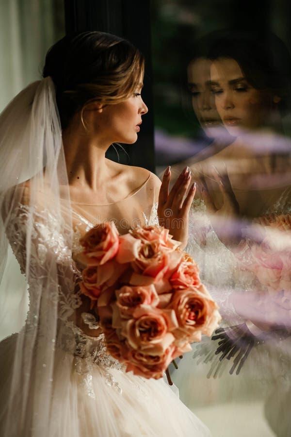 Schöne junge Braut mit dunklem Haar in luxuriösem Hochzeitskleid mit Blumenstrauß lizenzfreie stockfotos