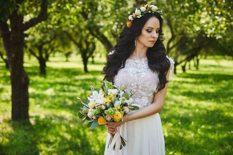 Schöne junge Braut mit einem Blumenkranz in ihrer Hochzeitsfrisur und in einem stilvollen Kleiderholdingblumenstrauß von Blumen lizenzfreies stockbild