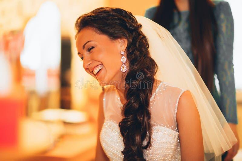 Schöne junge Braut mit Hochzeitsmake-up und -frisur im Schlafzimmer, abschließende Vorbereitung der Jungvermähltenfrau für die He lizenzfreies stockbild
