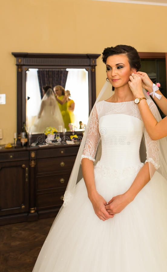 Schöne junge Braut mit Make-up und Frisur im Schlafzimmer, abschließende Vorbereitung der Jungvermähltenfrau für die Heirat lizenzfreies stockfoto