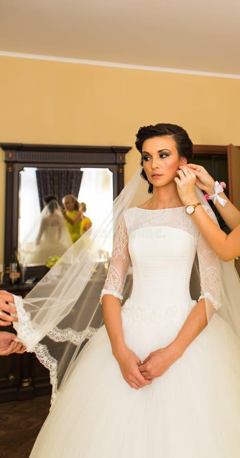 Schöne junge Braut mit Make-up und Frisur im Schlafzimmer, abschließende Vorbereitung der Jungvermähltenfrau für die Heirat lizenzfreie stockfotografie