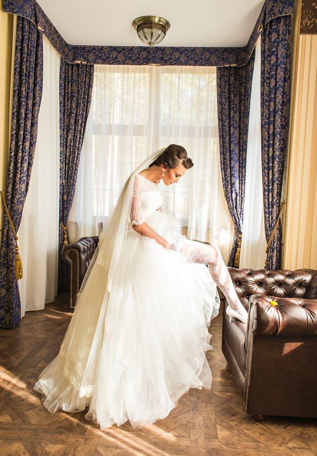 Schöne junge Braut mit Make-up und Frisur im Schlafzimmer, abschließende Vorbereitung der Jungvermähltenfrau für die Heirat lizenzfreie stockfotos