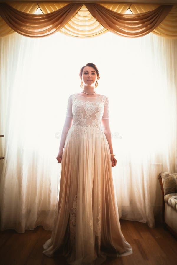 Schöne junge Braut nahe dem Fenster im vollen Wachstum stockbild
