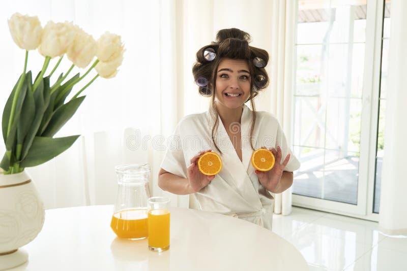 Schöne junge brunette Frau in den Haarlockenwicklern, die Orangen in beiden Händen nahe ihren Brüsten im hellen Küchenschauen hal stockfotos