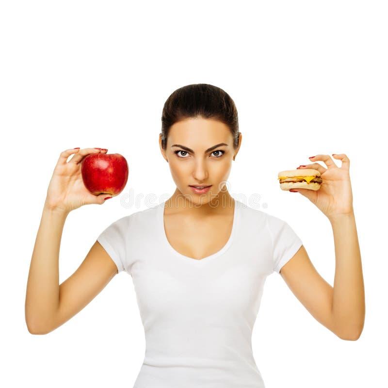 Schöne junge brunette Frau in weißen T-Shirt Griffen Apfel und Hamburger Stände, die das Lächeln auf weißem Hintergrund aufwerfen stockbilder