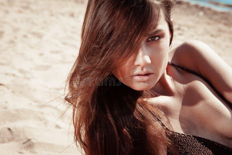Schöne junge Brunettefrau auf einem sonnigen Strand lizenzfreie stockbilder
