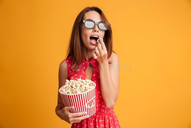 Schöne junge Brunettefrau in den Gläsern 3d und im roten Kleid-eatin lizenzfreies stockfoto