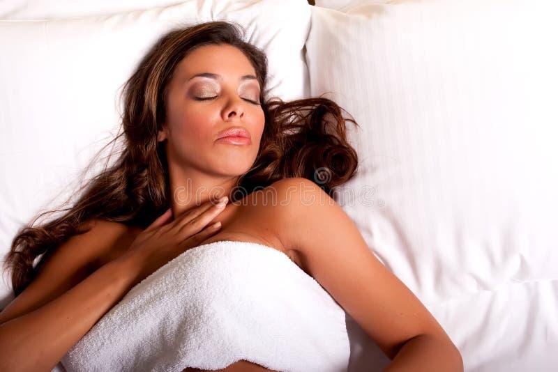 Schöne junge Brunettefrau, die auf dem Bett sich entspannt stockfotografie