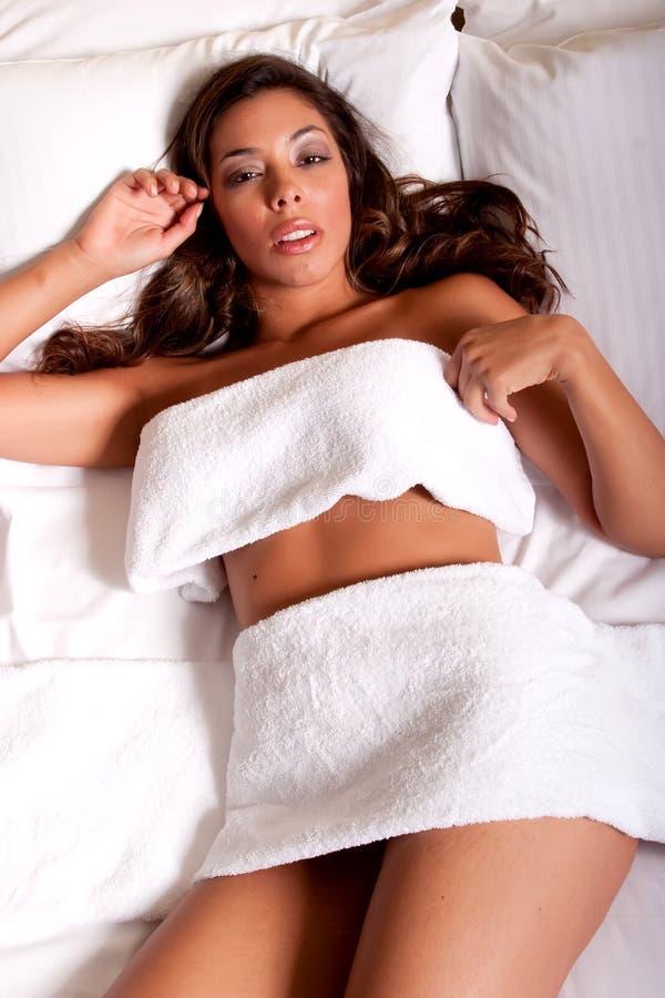 Schöne junge Brunettefrau, die auf dem Bett sich entspannt stockbilder