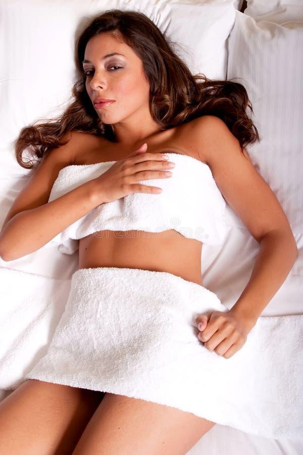 Schöne junge Brunettefrau, die auf dem Bett sich entspannt lizenzfreie stockfotografie