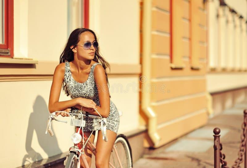Schöne junge Brunettefrau, die auf einem Fahrrad in der alten Stadt sitzt stockfoto