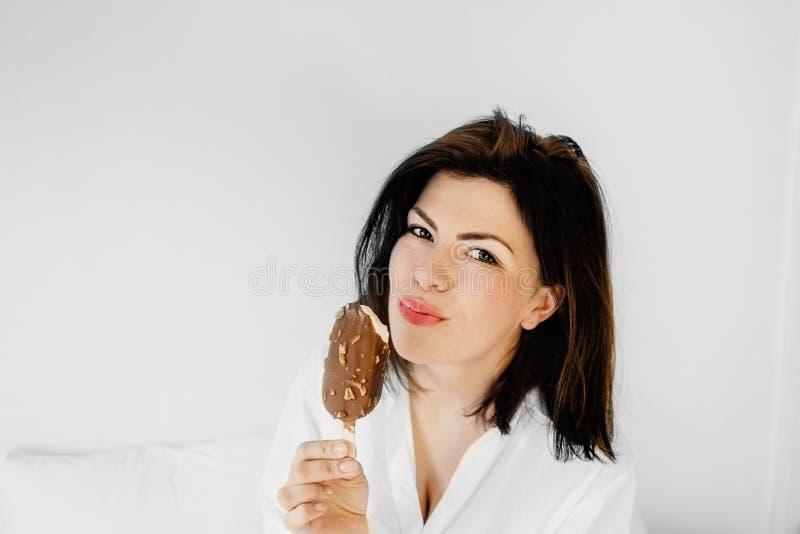 Schöne junge Brunettefrau, die Auffrischungseiscreme hat Happ lizenzfreie stockfotos