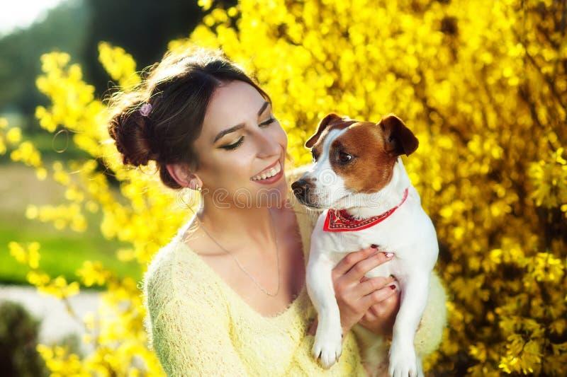 Schöne junge Brunettefrau, die draußen im Park zusammen mit ihrem herrlichen Jack Russell-Terrier genießt lizenzfreies stockfoto