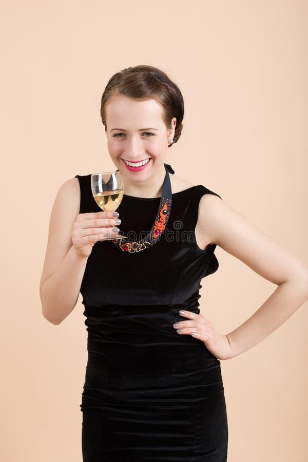 Schöne junge Brunettefrau, die ein Glas Weißwein hält lizenzfreies stockbild