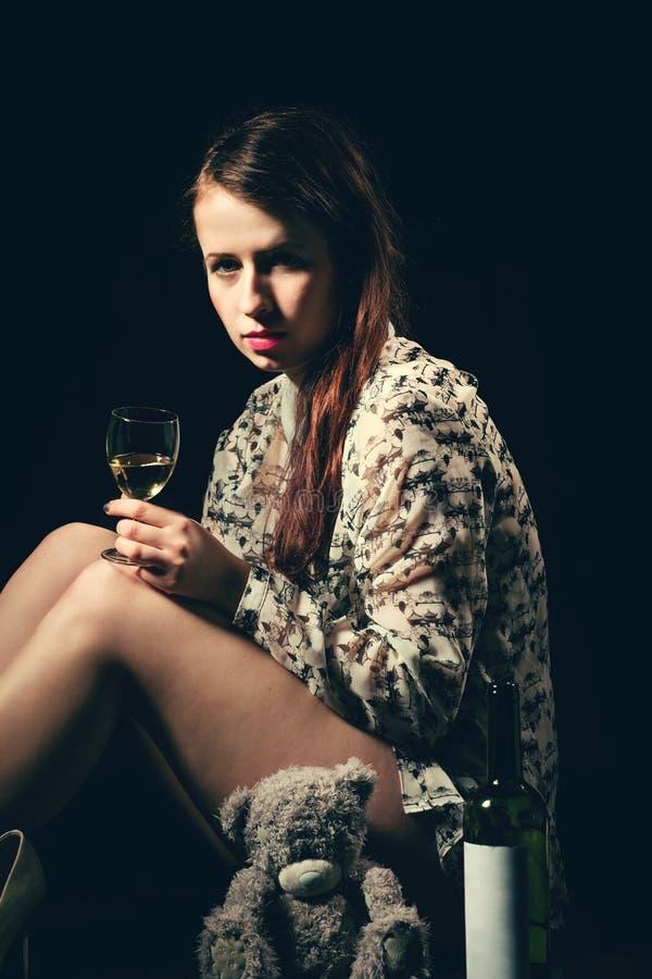 Schöne junge Brunettefrau, die eine Flasche Weißwein hält stockfotografie