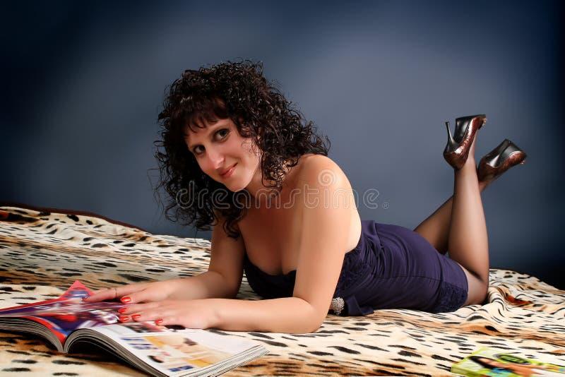 Schöne junge Brunettefrau, die eine Zeitschrift liest lizenzfreie stockfotos