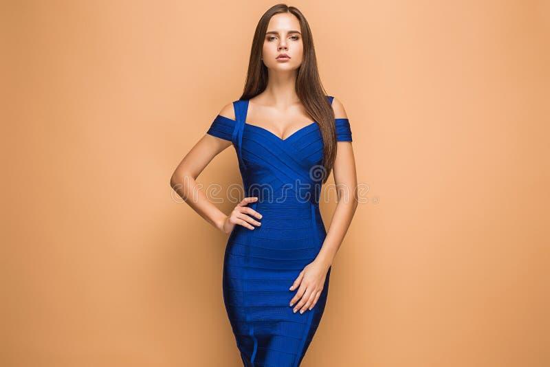 Schöne junge Brunettefrau, die in einem blauen Kleid aufwirft studio lizenzfreies stockbild