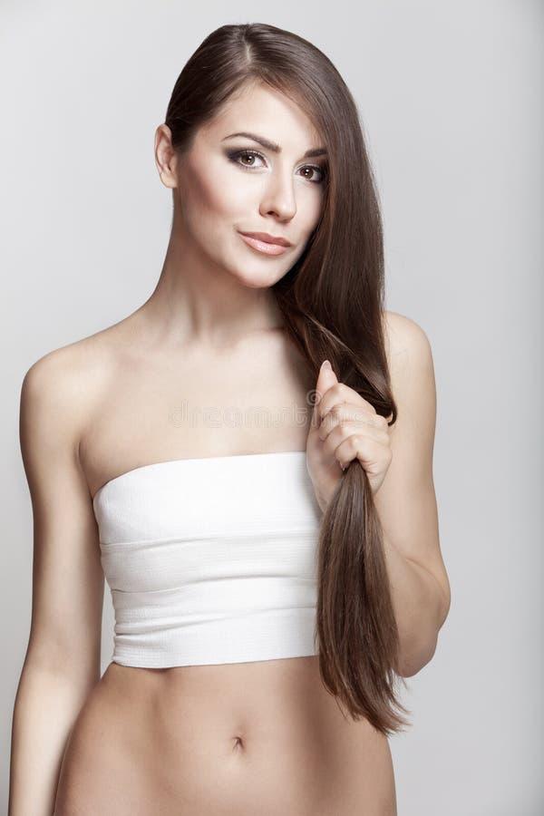 Schöne junge Brunettefrau, die ihr Haar hält lizenzfreie stockfotos