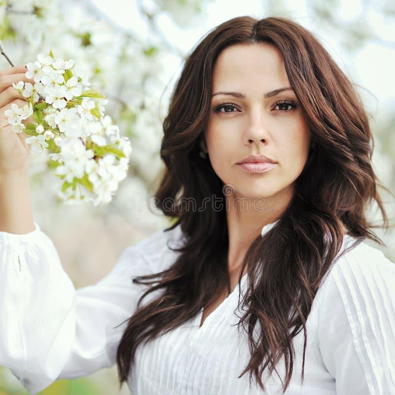 Schöne junge Brunettefrau, die nahe dem Apfelbaum - Cl steht stockbilder