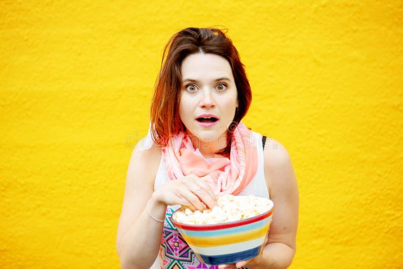 Schöne junge Brunettefrau, die Popcorn isst stockfotos