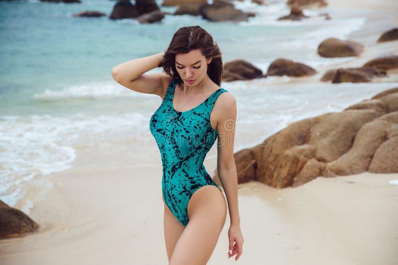 Schöne junge Brunettefrau im blauen Bikini, der auf dem Strand aufwirft Sexy vorbildliches Porträt mit perfektem Körper Konzept v stockbilder