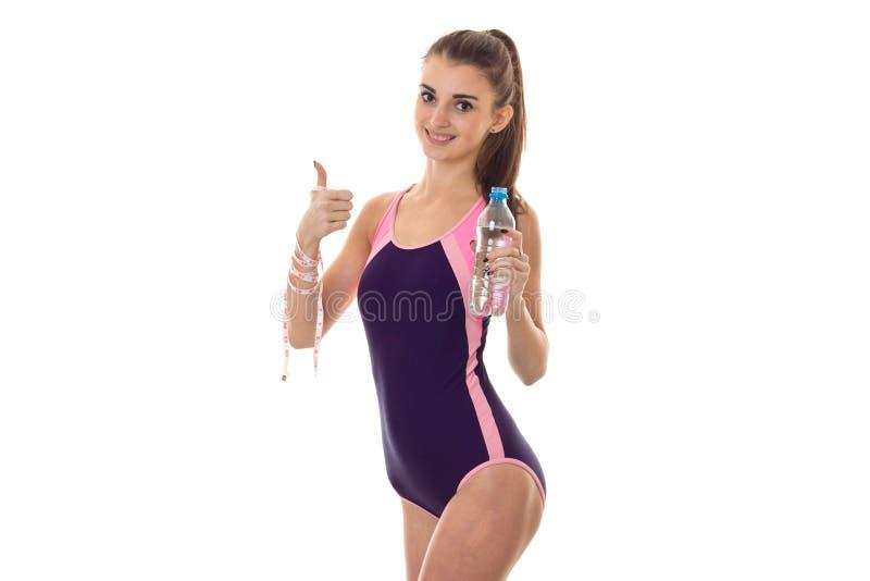 Schöne junge Brunettefrau im Körperbadeanzug, der auf Kamera mit Maßband in einer Hand und in Flasche von aufwirft und lächelt stockbilder