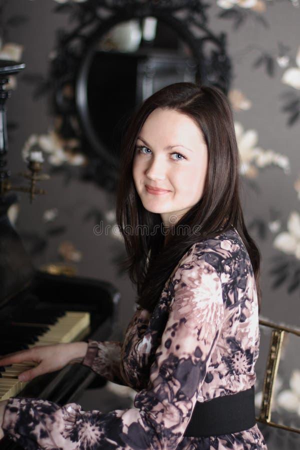 Schöne junge Brunettefrau im Kleid spielt Klavier lizenzfreies stockfoto