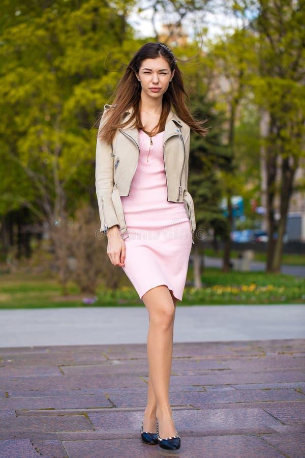 Schöne Junge Brunettefrau Im Rosa Kleid Und In Der Grauen Jacke ...