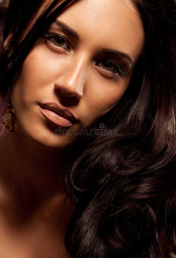 Schöne junge Brunettefrau mit dem lockigen Haar lizenzfreies stockbild