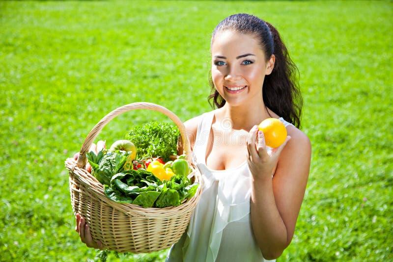 Schöne junge Brunettefrau mit einem Weidenkorb voll vom vege lizenzfreie stockfotos